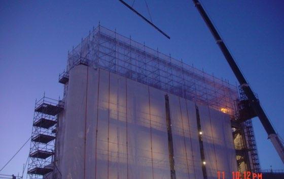 Väderskydd och ställning monteras på en industribyggnad i kvällsljus.