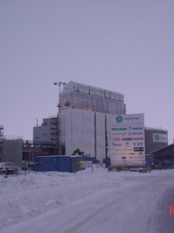 Väderskydd och ställning monteras på en industribyggnad.