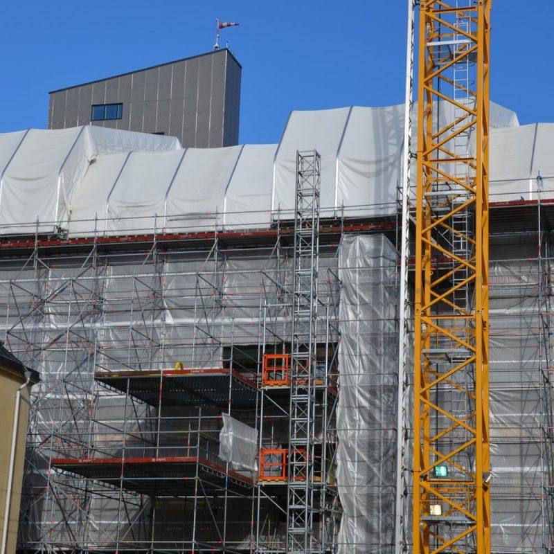 Bild på väderskydd som skyddar medarbetare från väderstänk under arbete på byggnadsställning.