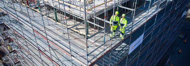 Två byggarbetare ler glatt mot en kamera medan de står på en byggnadsställning.