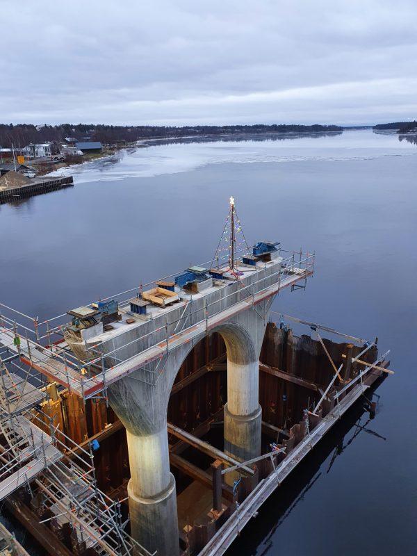 Montage av ställning pågår inför byggnation av ny bro över Kalix älv, med vy över vattnet.