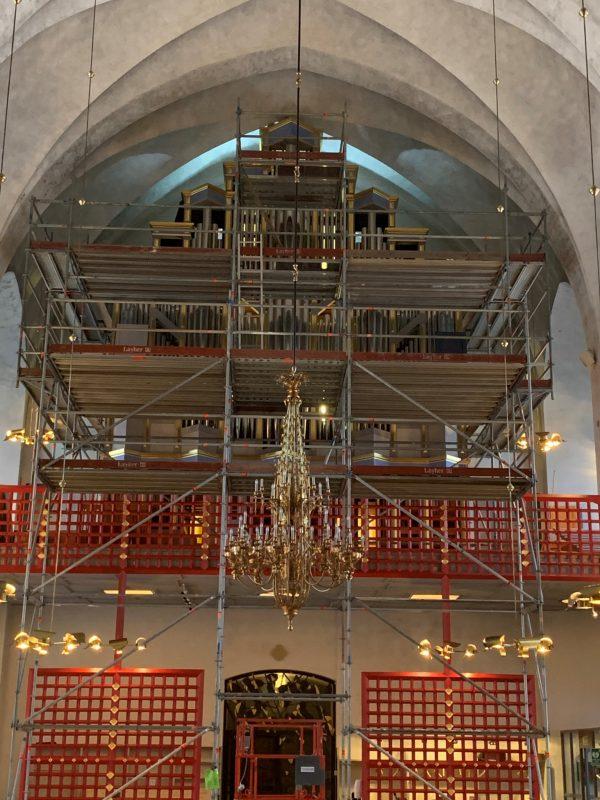 Inuti en kyrka, där ställning har monterats för att renovera en orgle.