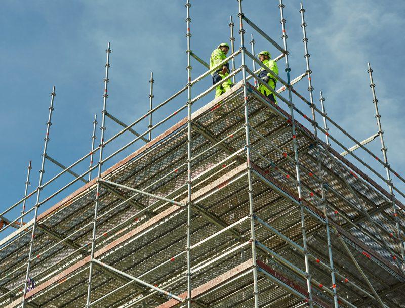 Två byggarbetare står på toppen av en byggnadsställning.